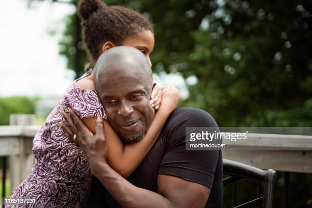 rapariga com o autismo que abraça o pai ao ar livre. - autismo - fotografias e filmes do acervo