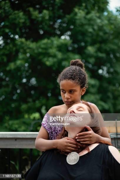 Niña con autismo abrazando a la madre al aire libre.