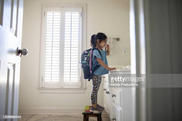 young girl with backpack brushing her teeth in bathroom - preparation stock pictures, royalty-free photos & images