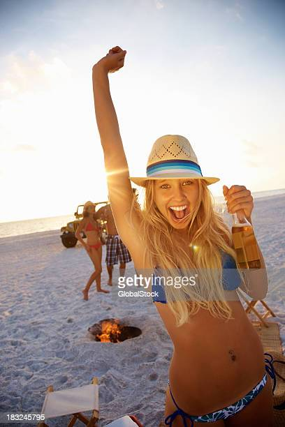 Young girl with beer and friends in background on beach