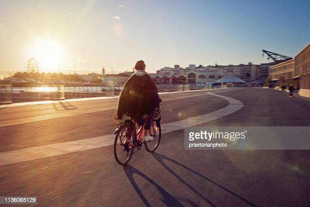 chica joven con bicicleta está disfrutando de la puesta de sol en la playa - valencia fotografías e imágenes de stock