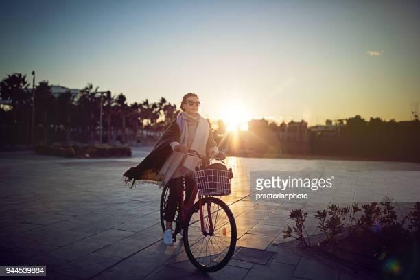 chica joven con la bicicleta está disfrutando de la puesta de sol en la playa - montar fotografías e imágenes de stock
