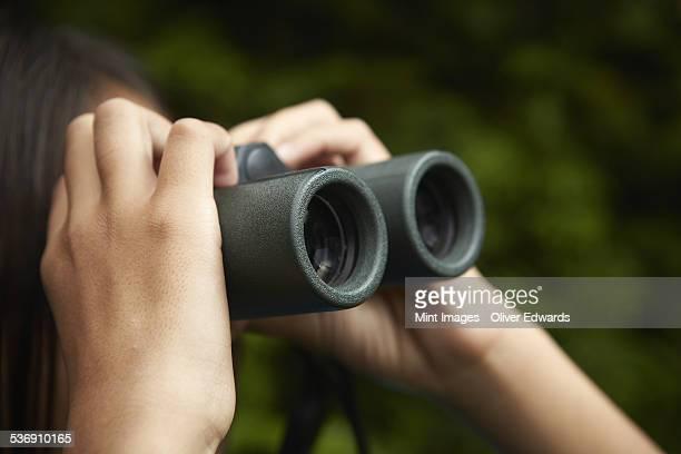A young girl with bird watching binoculars.