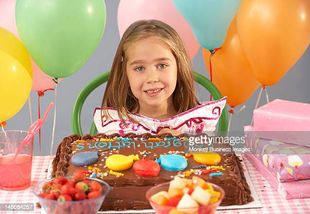 Young girl with birthday cake and gifts at party