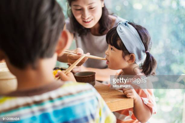 Young Girl With Black Pigtails And Blue Hairband Boy And Woman Sitting At A Table