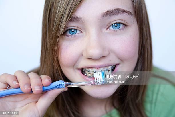 Giovane ragazza con occhi azzurri Lavarsi i denti con bretelle.