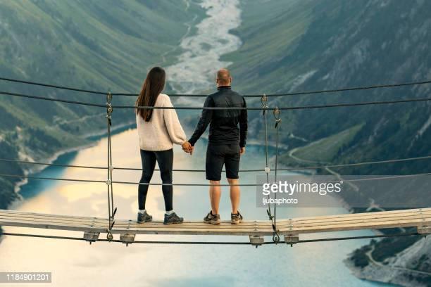 アルプスのロープブリッジに立っているボーイフレンドを持つ若い女の子 - 北チロル ストックフォトと画像