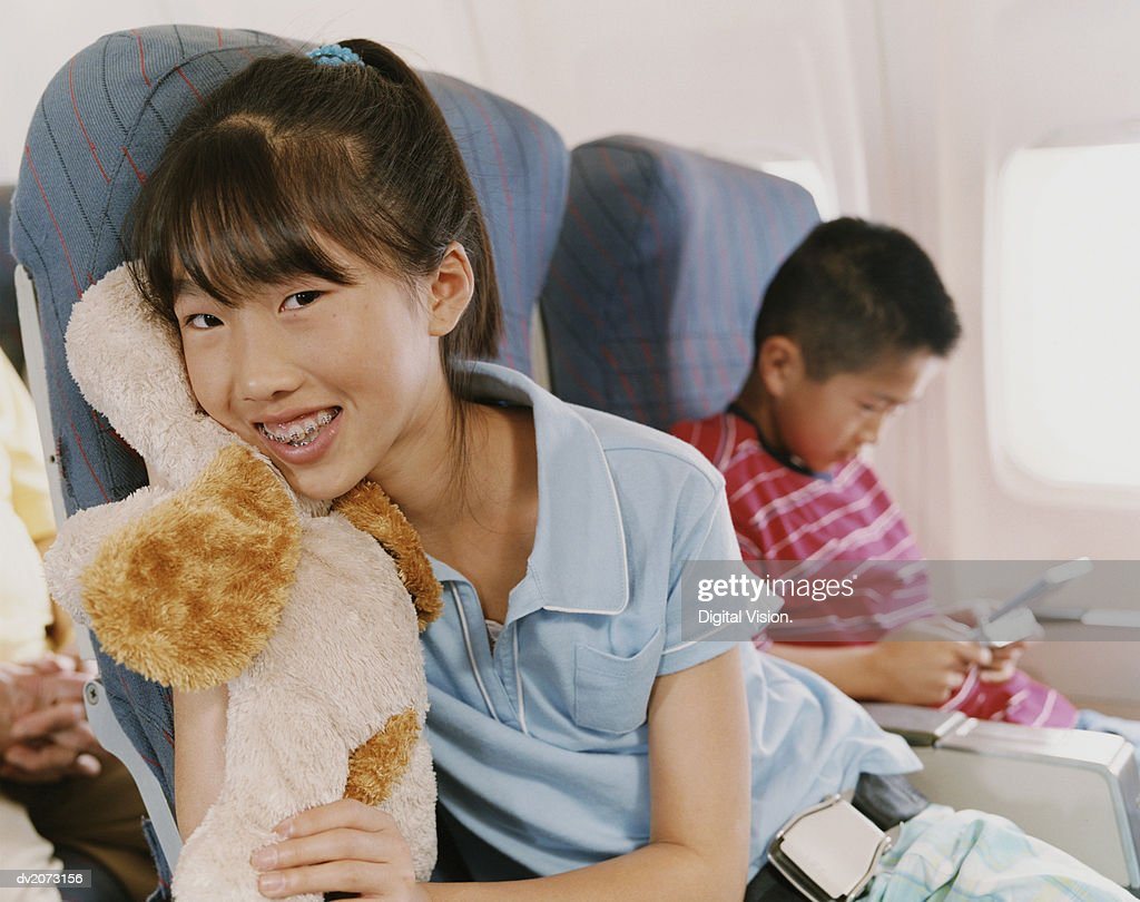 Young Girl With Braces Sits in a Plane Holding a Cuddly Toy : Stock Photo