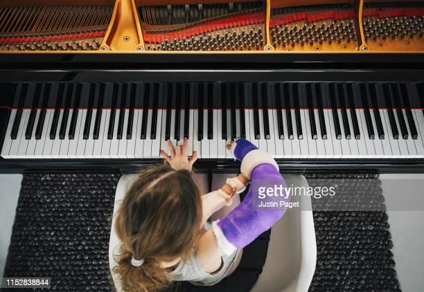 young girl with broken arm playing piano - entertainment occupation stock pictures, royalty-free photos & images
