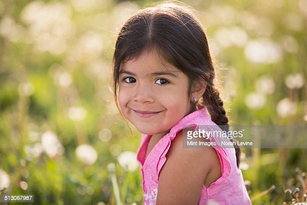 A young girl with brown hair and braids, in a wild flower meadow.