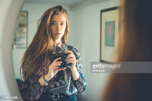 young girl with camera in hand stands in front of the mirror, takes a selfie - mirror selfie stock pictures, royalty-free photos & images