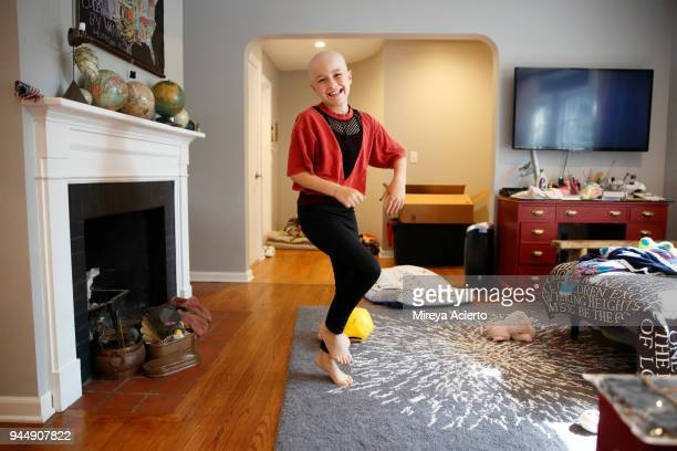 a young girl with cancer, dancing in a living room, with a big smile. - cancer illness stock pictures, royalty-free photos & images