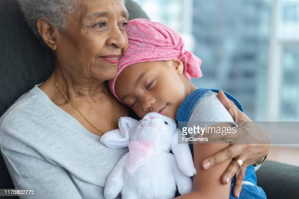 young girl with cancer hugs grandmother lovingly - fat granny stock pictures, royalty-free photos & images