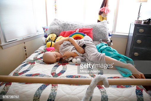 A young girl with cancer, lays on her bed looking a little nervous,  surrounded by pillows and stuffed animals.