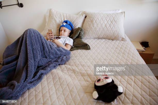 a young girl with cancer, plays on her phone, lying on a bed with a stuffed animal. - ann arbor stock pictures, royalty-free photos & images