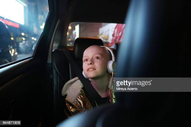 a young girl with cancer, riding in a car, looks at all the bright lights of the city. - cancer stock photos and pictures