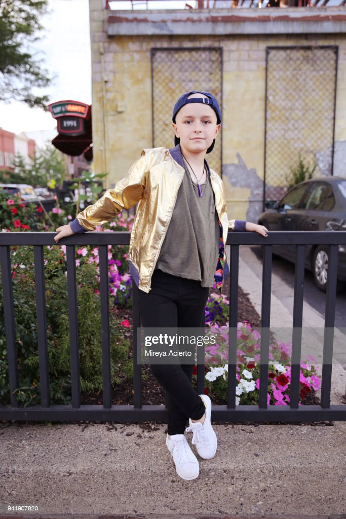 A young girl with cancer, wearing a gold jacket, posing in front of a metal gate. : Stock Photo
