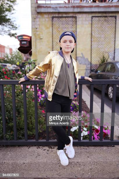 A young girl with cancer, wearing a gold jacket, posing in front of a metal gate.