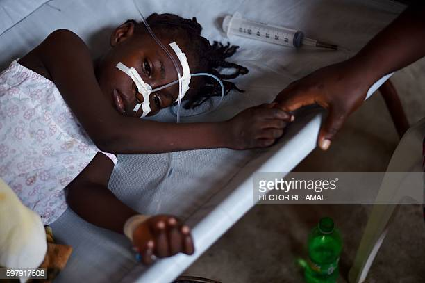 A young girl with cholera symptoms is treated at the Cholera Treatment Center of Diquini in PortauPrince Haiti on 23 August 2016 The cholera epidemic...