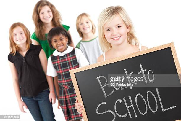 Junges Mädchen mit Klassenkameraden und zurück zur Schule auf Tafel