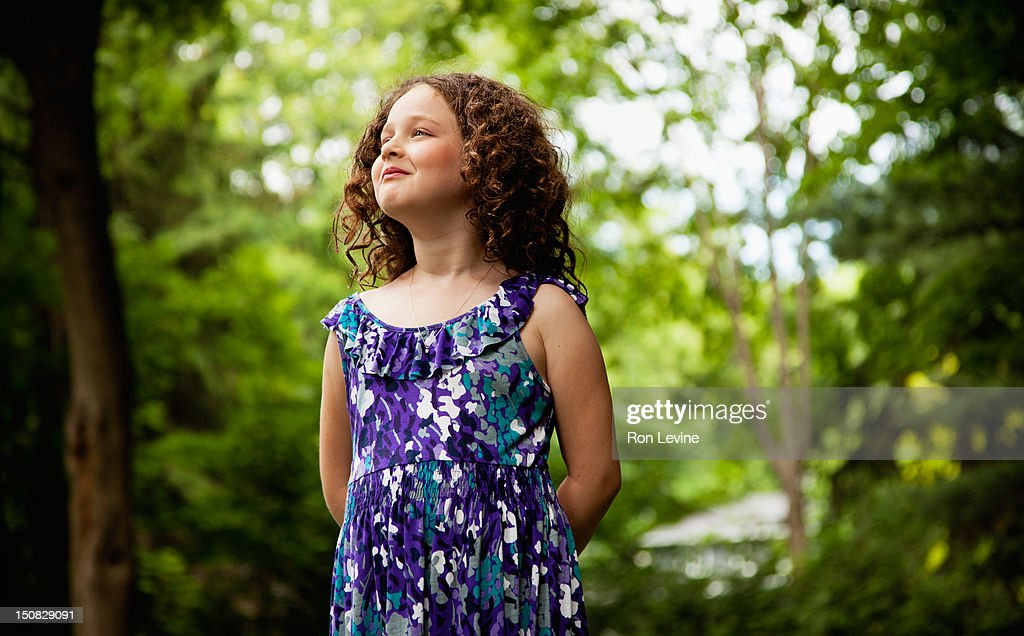 Young girl with curly hair, looking away : Stock Photo