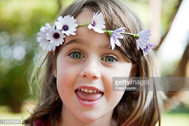 Young girl with daisy chain on head, portrait
