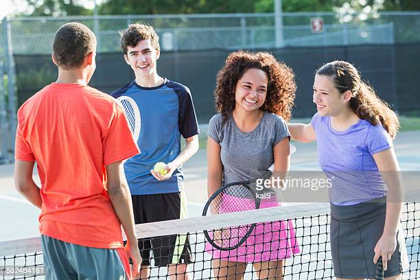 Young girl with disability playing tennis with 3 friends