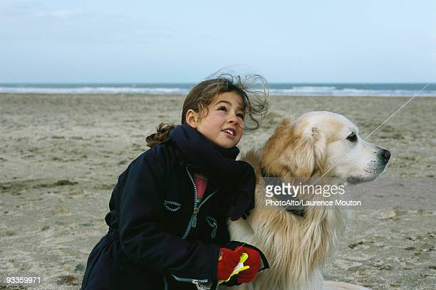 Young girl with dog on beach flying kite