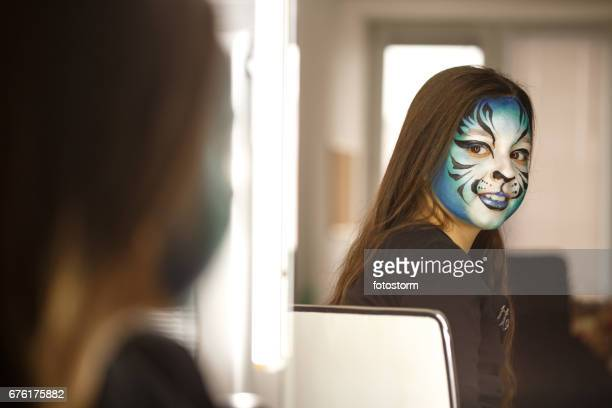 Young girl with face painted admiring herself in mirror