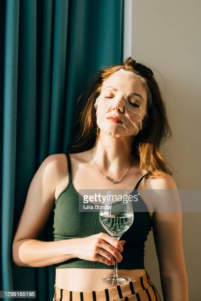 young girl with facial mask looking holding glass of water. - indulgence stock pictures, royalty-free photos & images