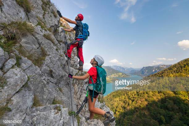 young girl with father is climbing to the top of a mountain in alps - arrampicata su roccia foto e immagini stock