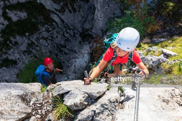 young girl with father is climbing to the top of a mountain in alps - outdoor pursuit stock pictures, royalty-free photos & images