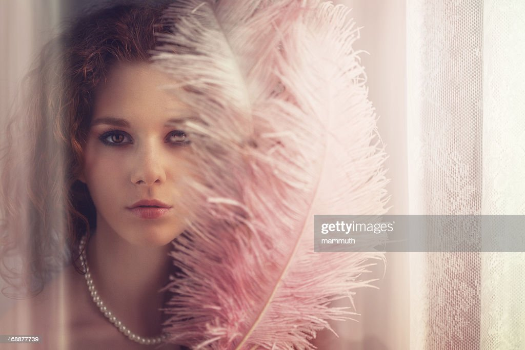 young girl with feather fan by the window : Stock Photo