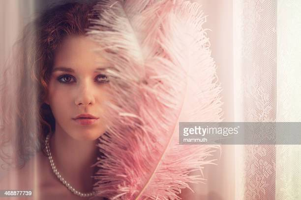 young girl with feather fan by the window