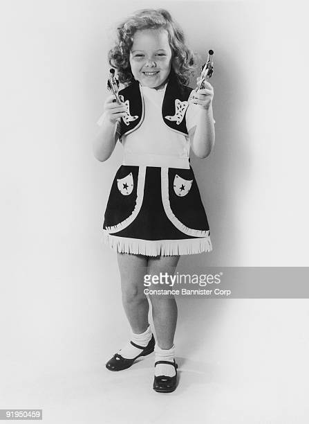 young girl with guns drawn and cowgirl dress - {{ contactusnotification.cta }} stockfoto's en -beelden