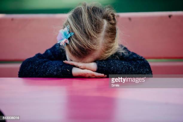 young girl with head on hands sitting at pink table - manos a la cabeza fotografías e imágenes de stock