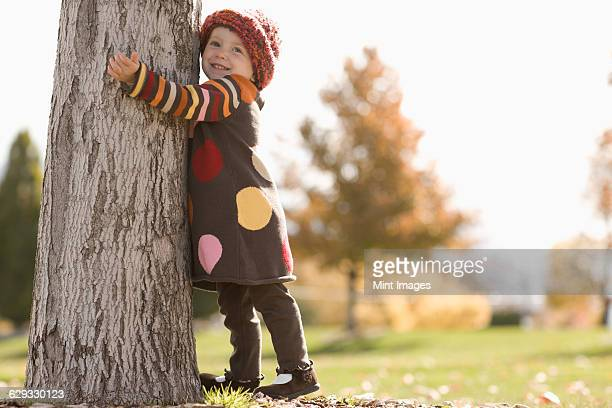 A young girl with her arms around a tree in autumn sunshine