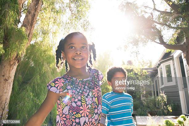 Young girl with her brother playing in garden sunlight