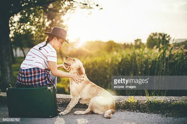 young girl with her dog in the sunset