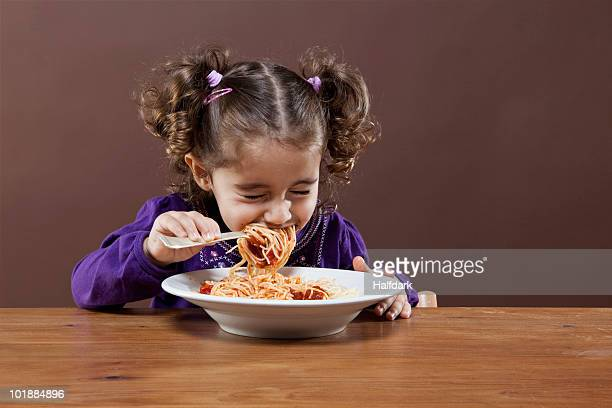 A young girl with her eyes shut tightly eating spaghetti, studio shot