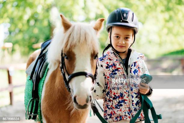 young girl with her pony horse - riding hat stock pictures, royalty-free photos & images