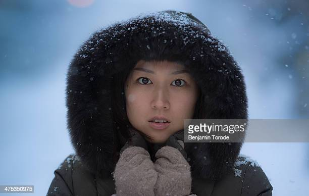 Young girl with hood in falling snow