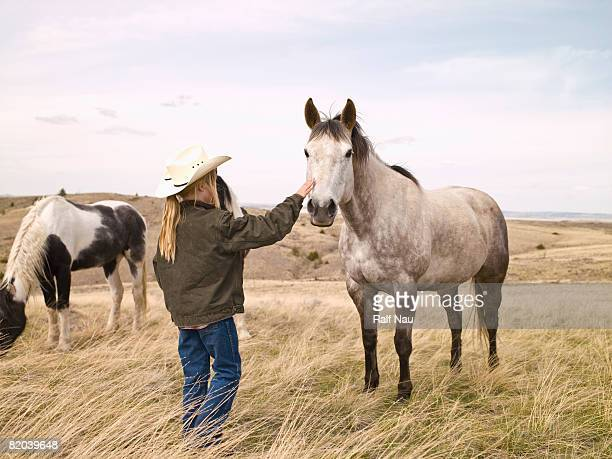 Young girl with horse on ranch