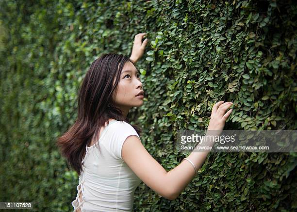 Young girl with ivy wall