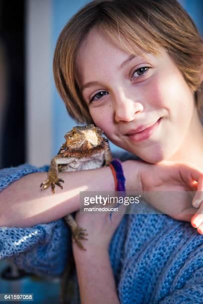 Young girl with lizard pet on shoulder in her bedroom.
