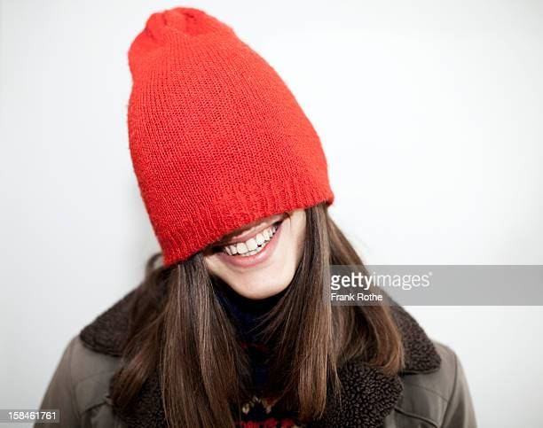 young girl with long brown hair and a red cap on