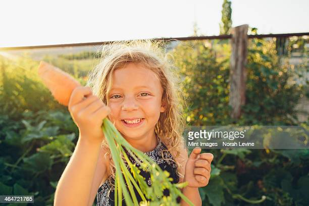 A young girl with long red curly hair outdoors in a garden holding a large fresh picked carrot.