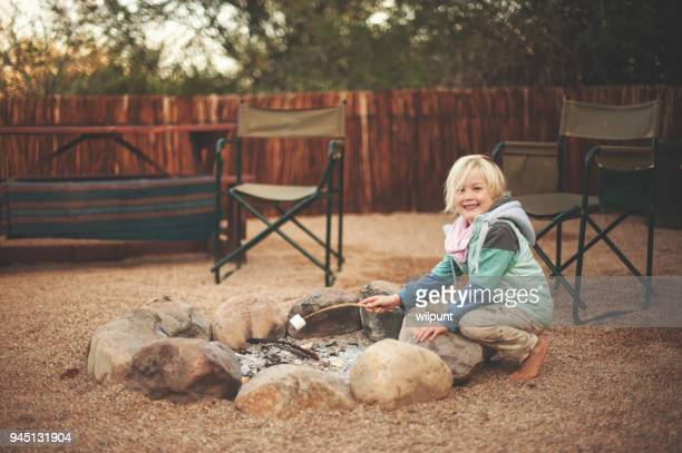 Young Girl with marshmallow on Camping Fire Smiling at Camera