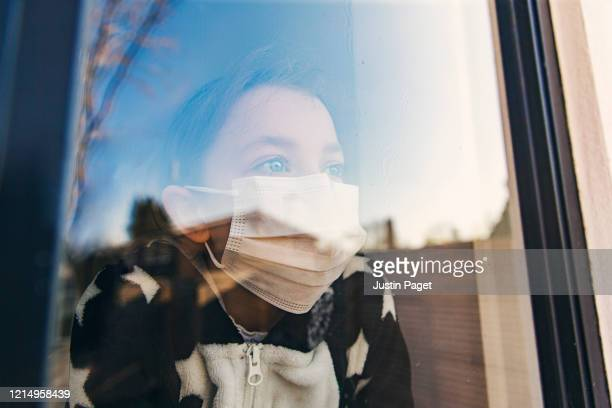 young girl with mask looking through window - protection stock pictures, royalty-free photos & images