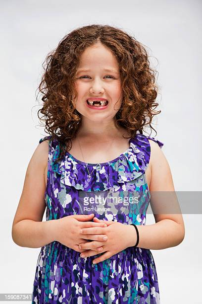 Young girl with missing teeth, ginning widely